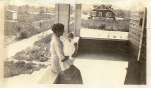 Dorothy's mother holding baby Erland (her firstborn), ca. 1917. House in the distance occupied by Murkve family.