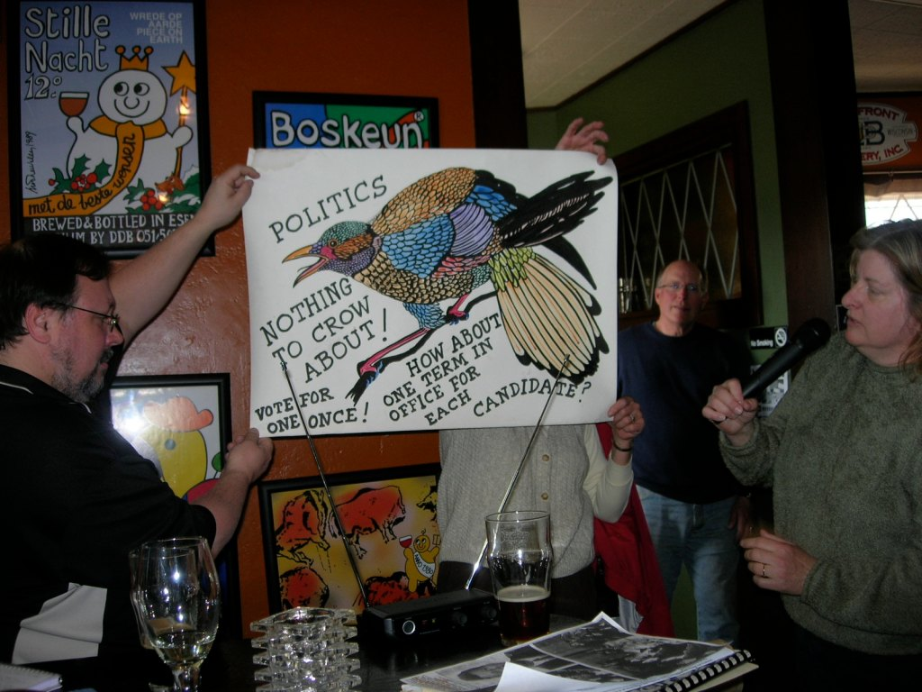 Bill Rogers and Pat Martin display a Sid Boyum political cartoon; Pete Fauerbach looks on from the background.