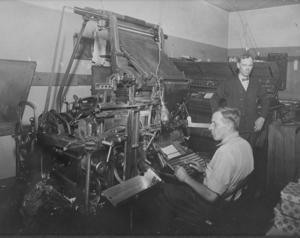 East Side Print Shop composing room with linotype machine and operators.