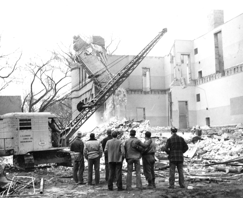 Crane knocking down the Marquette School building.  The man in the plaid jacket is identified in the newspaper as William Gutzmer, who lived at 1154 Jenifer St.
