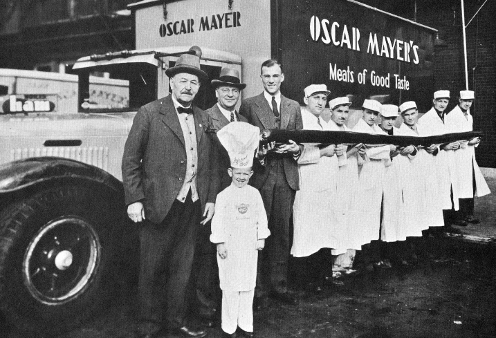 "Seven workers along with Oscar F. Mayer (left), Oscar G. Mayer (middle), Oscar G. Mayer Jr. (right) and Little Oscar (Meinhardt Raabe) hold the ""largest sausage in the world."""